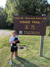 Girl and toy dog near trail sign