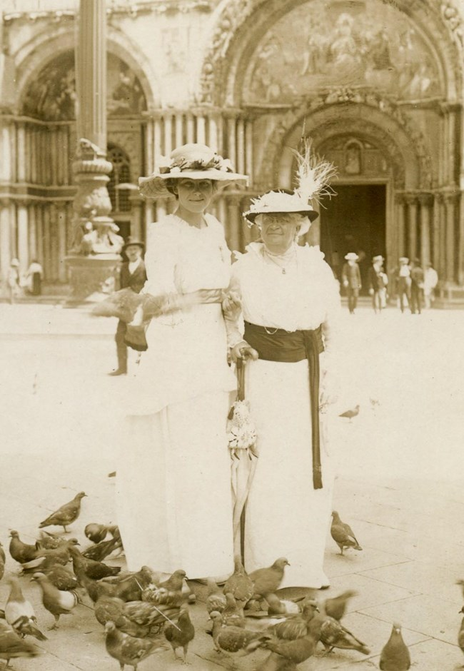 Two women in white dresses and hats standing in public square surrounded by pigeons.