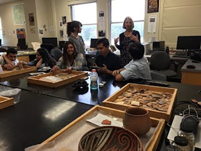 Students work on archeological artifacts in a lab