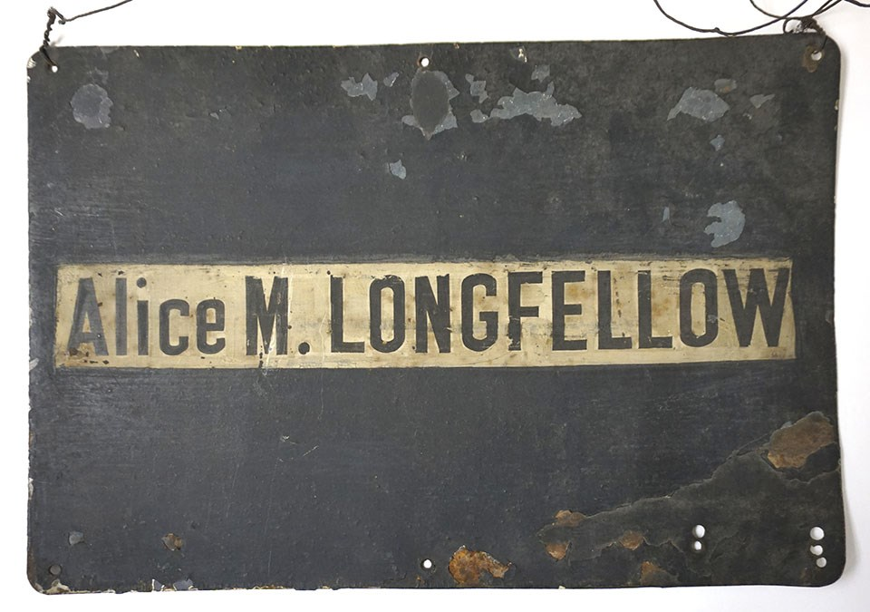 "Black rectangular sign with white stripe, letters ""Alice M. LONGFELLOW"" at center."