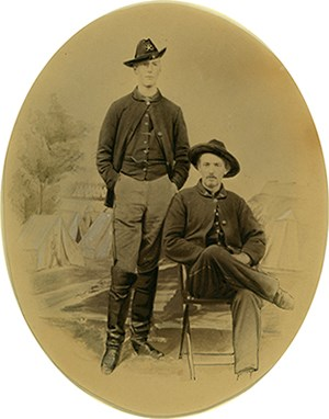 Studio portrait of two young men in Civil War uniform in front of painted backdrop with camp scene