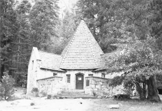 lodge with conical-shaped roof, surrounded by trees