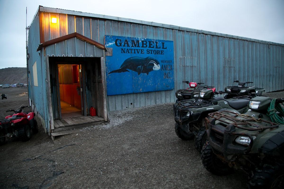 "A blue rectangular building with a small entry way into a red interior is lit up with a single light. A sign read,""Gambell Native Store""."
