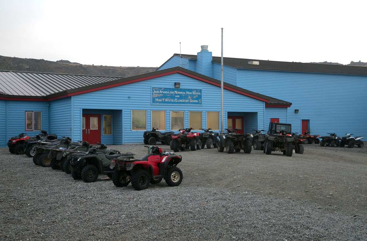 "A long blue multistory building stretches across the horizon. A sign reads, ""John Apangalook Memorial High School and Hugo T. Apatiki Elementary School"". Numerous ATVs are neatly parked in front of the school."