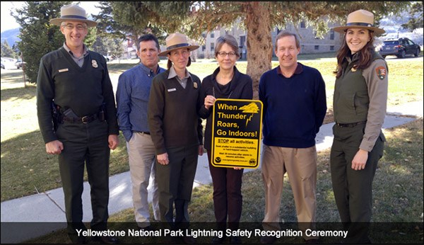Park rangers and representatives from NOAA holding lightning safety sign