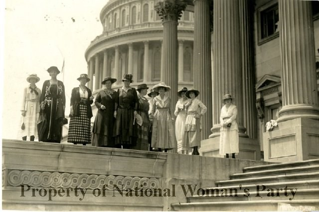 Ten women suffragists with Capitol dome in background