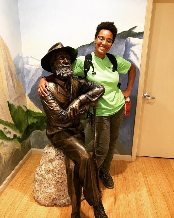 A young woman stands next to a John Muir statue.