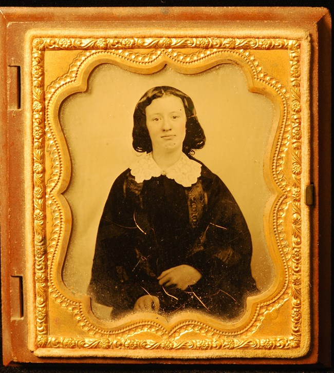 Ambrotype photograph portrait of a young woman in a dark dress with a white lace collar