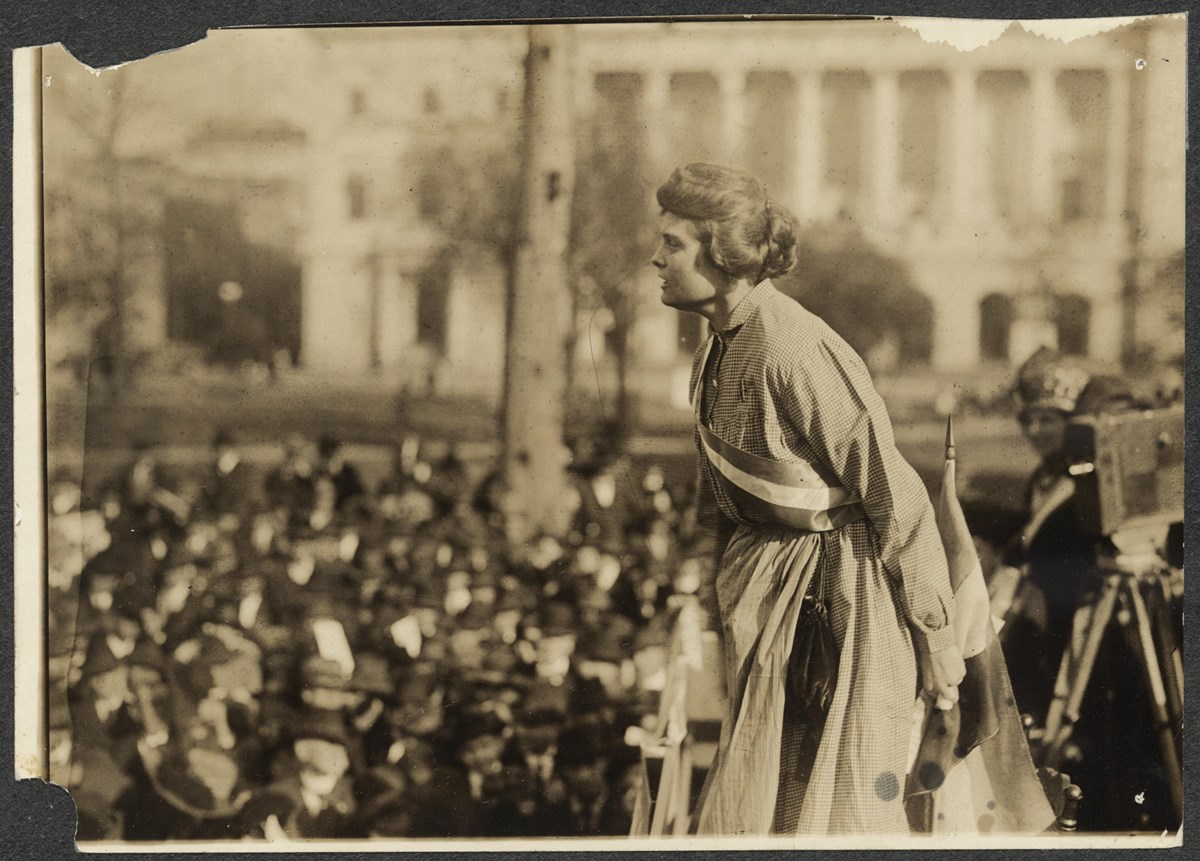 "Photograph of Lucy Branham speaking at outdoor meeting during the NWP ""Prison Special"" tour. Branham is above a large crowd, wearing prison dress and suffrage sash, with suffrage flag and camera on tripod behind her (right)."