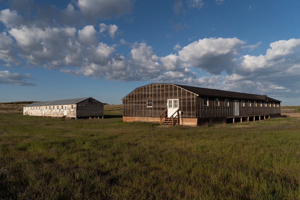 Two long wooden buildings on a grass field