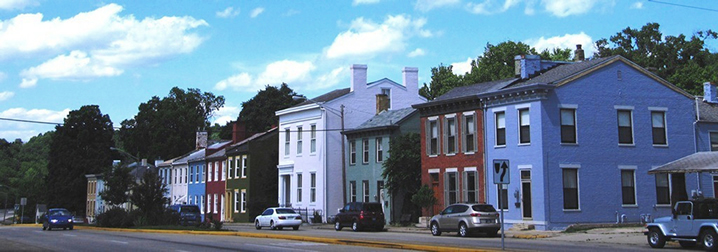 Colorful town house fronts with a street in front.