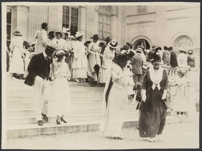 Photograph of women and men on steps leading up to Marble House, Alva Belmont's estate in Newport, RI.