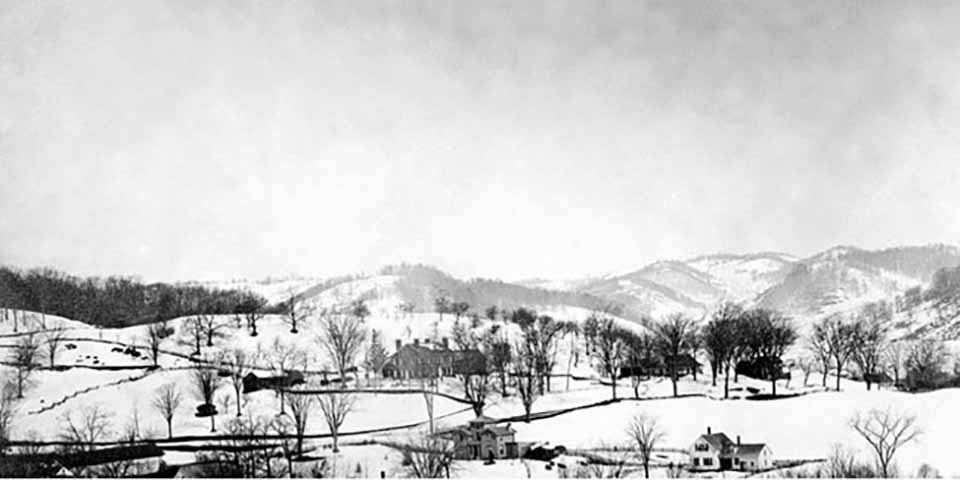 Black and white photo of a small town with a mountain in the distance.