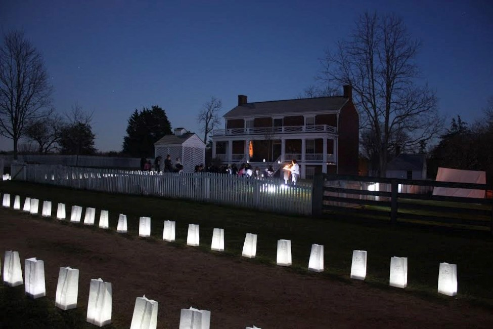 A small two story historic home with a small white fence. Paper Luminaries line the front yard at night.