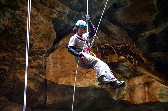 scientist rappelling on a climbing rope