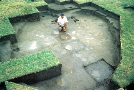 A man sitting in the remnants of an ancient house.