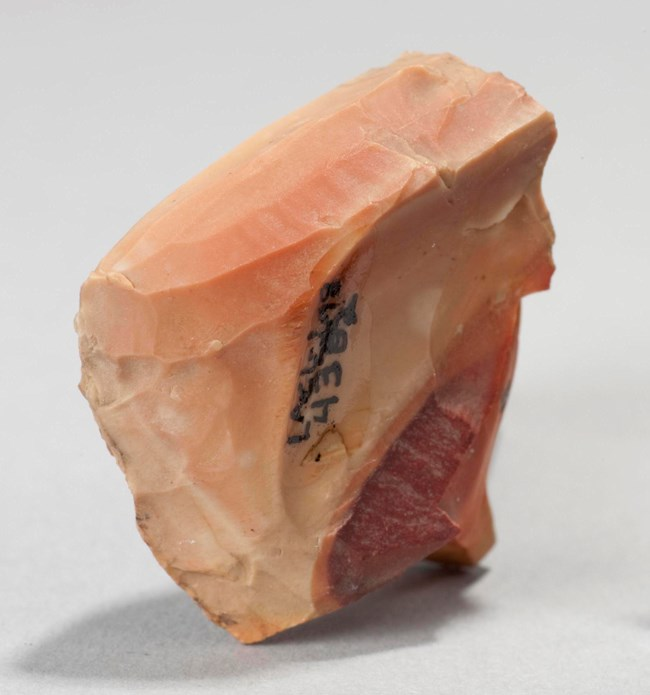Image of an archeological artifact, a peach colored stone with lines, arrow points.