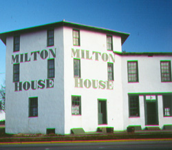 White, stone house with green painted words that say Milton House.