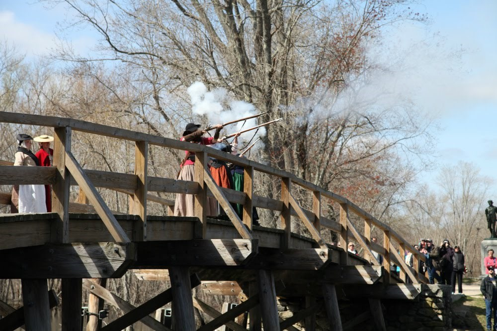 Women in period costumes fire guns while standing on wooden bridge.
