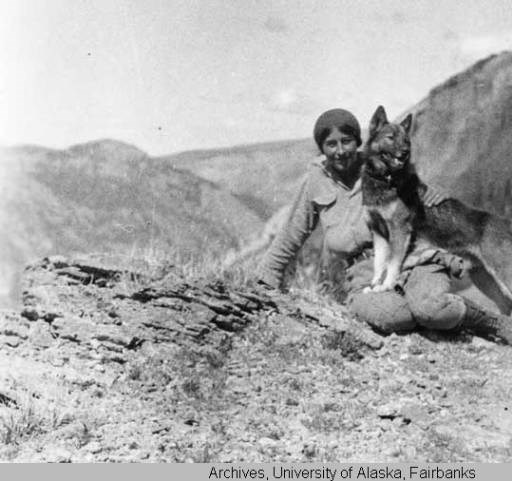 a woman sitting on a mountain top with a dog