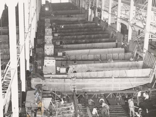 Photograph from balcony of large manufacturing structure. Workers assemble a tank landing craft in foreground. In background is a long line of assembled landing craft.