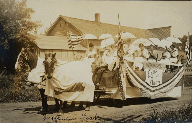 "Two horses pull a float carrying about ten women in white holding parasols. Sign reads ""Nebraska Next: Equal Rights."""