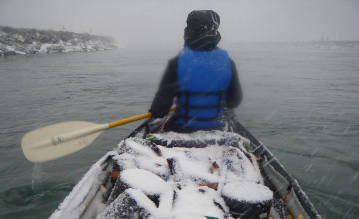 A person sits in a canoe paddling along a river forward as snow falls, creating a layer of white on all the gear packed in the boat