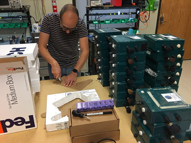 A National Park Service acoustic specialist prepares audio recording equipment and packaging for national parks participating in the Eclipse Soundscapes project.