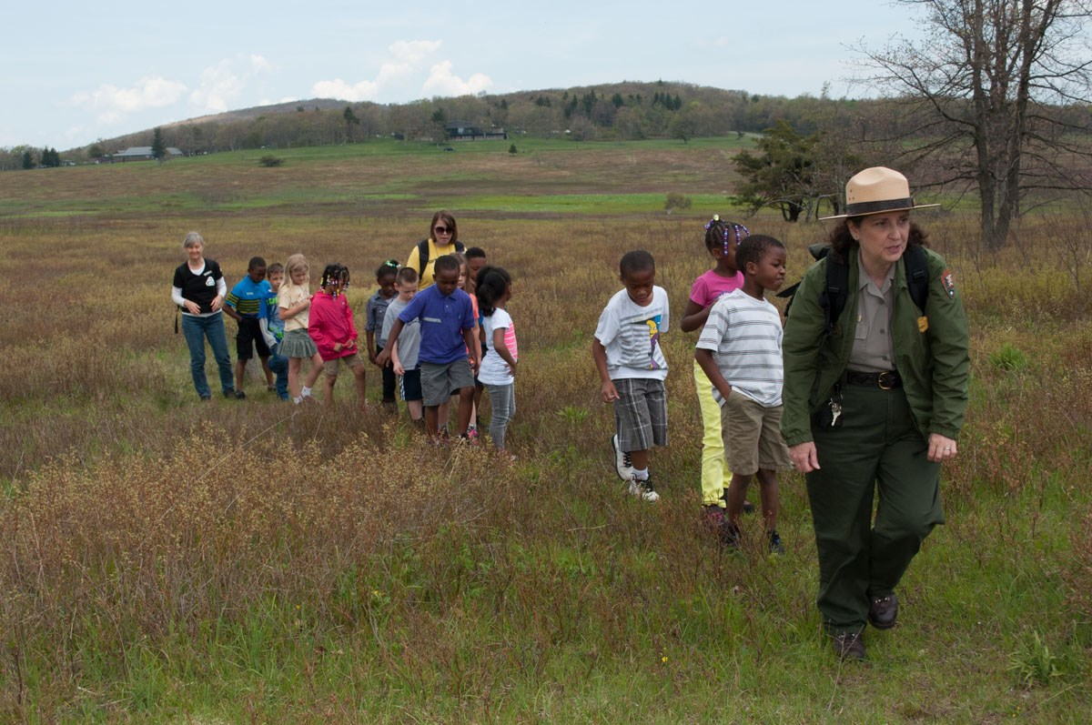 A group of students out on a hike with their chaperones and a park ranger.