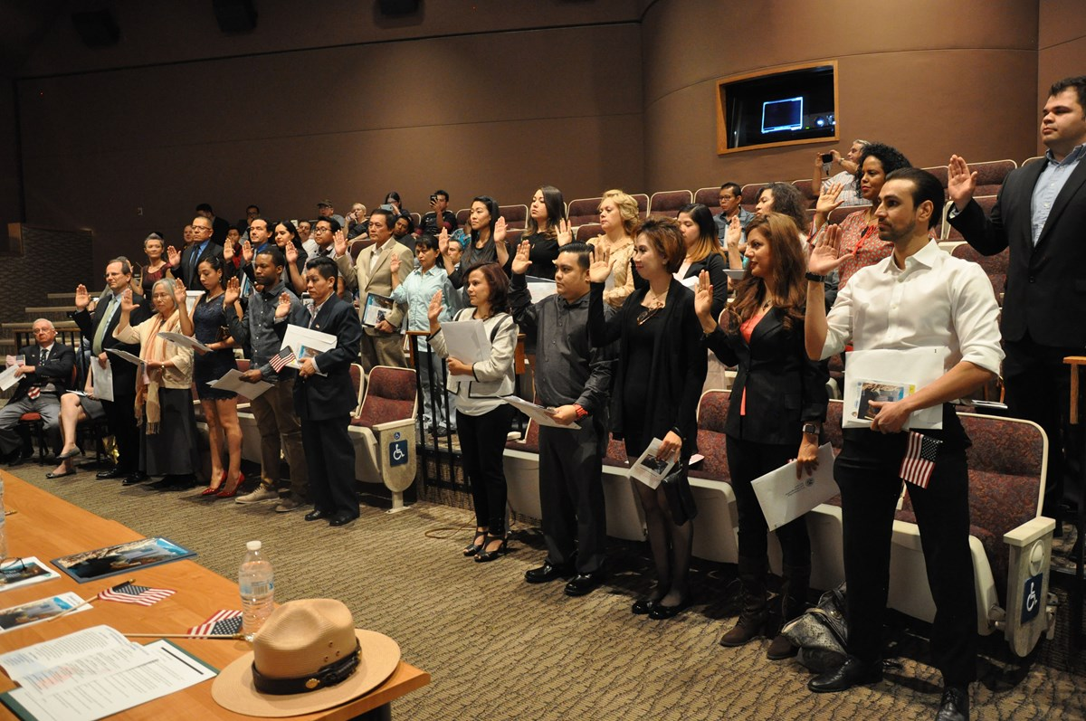 24 new citizens raise their right hands during naturalization ceremony in Hoover Dam auditorium.