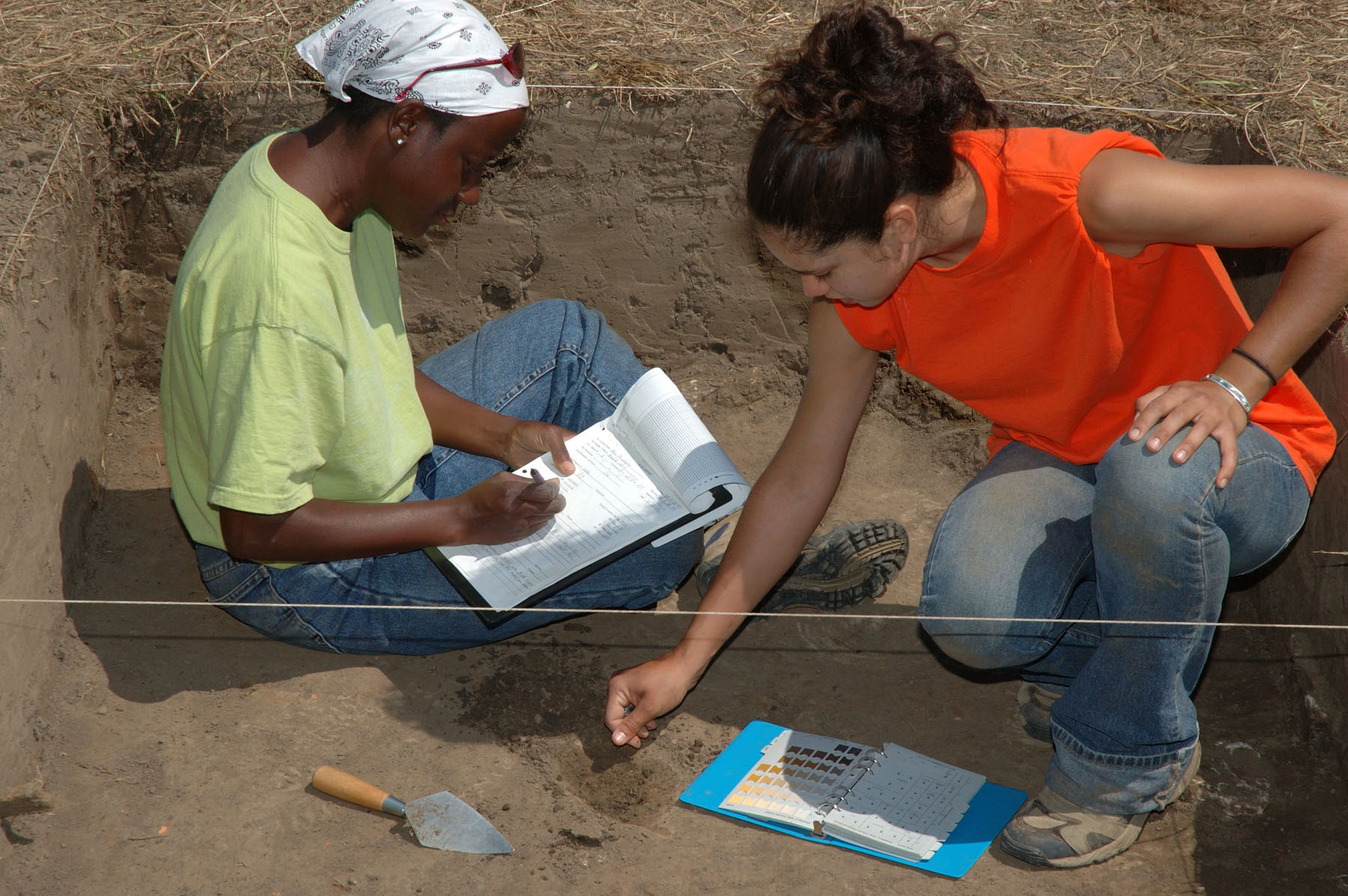 Two women writing on paper in a dirt hole.