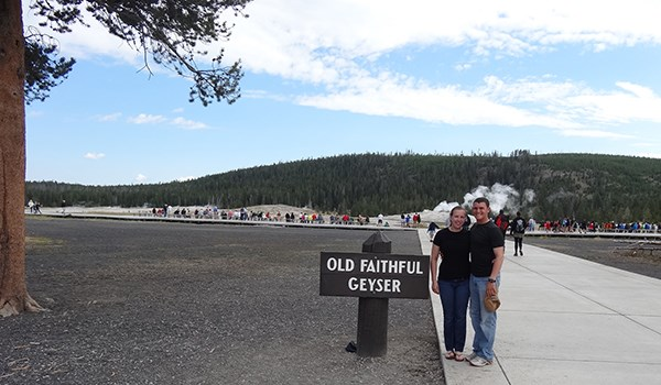 Couple stands by sign for Old Faithful Geyser