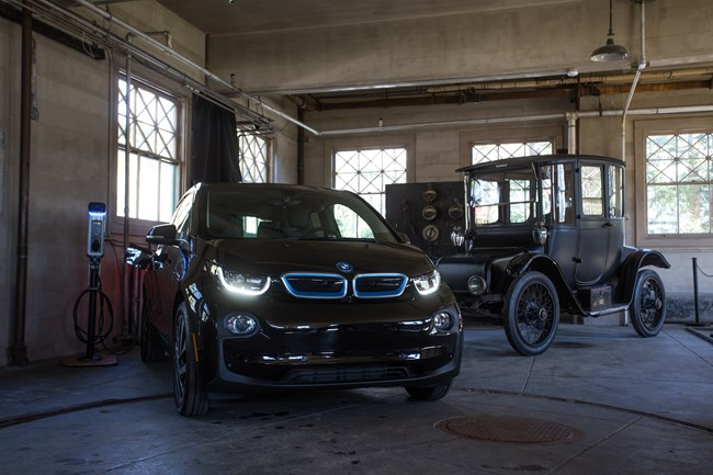 Modern electric vehicle manufactured by BMW (2017 i3) and Thomas Edison's 1917 Detroit Electric Model 47 and their charging stations inside Edison's Glenmont garage at Thomas Edison National Historical Park.