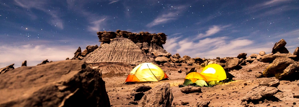 Several tents in a rocky desert under the stars at night