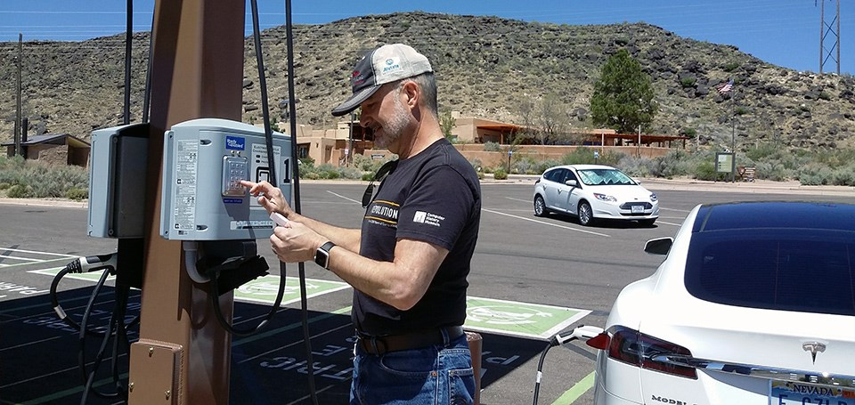 Visitor stands in parking lot and plugs in car to charging station