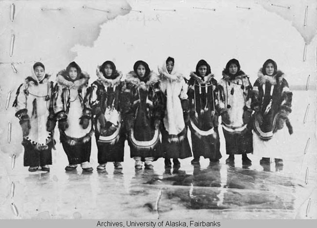 A group of Alaska Natives wearing furs look into the camera