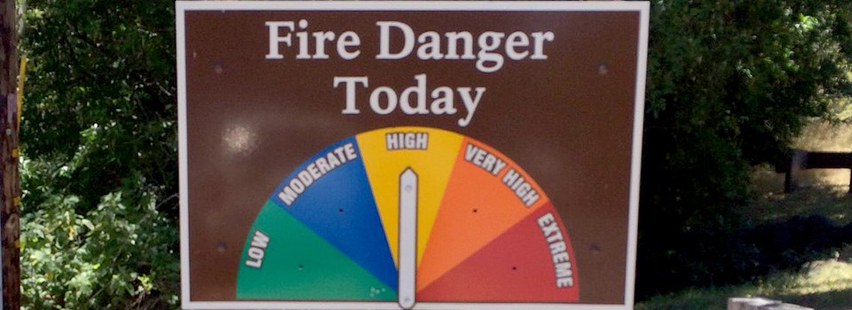 A sign with a half circle divided like a pie showing colors and words denoting fire danger.