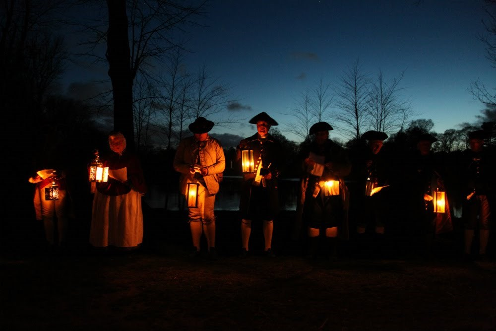 Men and women in period costumes hold lanterns at night.