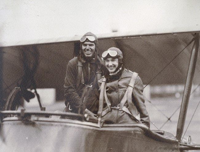 black and white photo of a man and woman wearing flight suits posing in a biplane