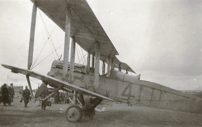 "Black and white photograph showing a DH-4 aircraft with the number ""4"" painted on its side."