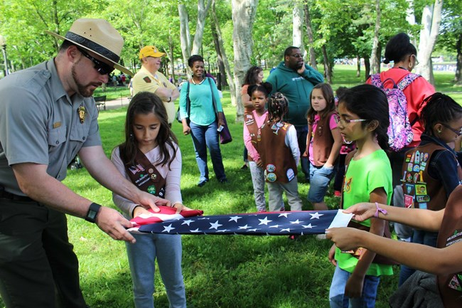 A ranger folds an American flag with a group of Girl Scouts