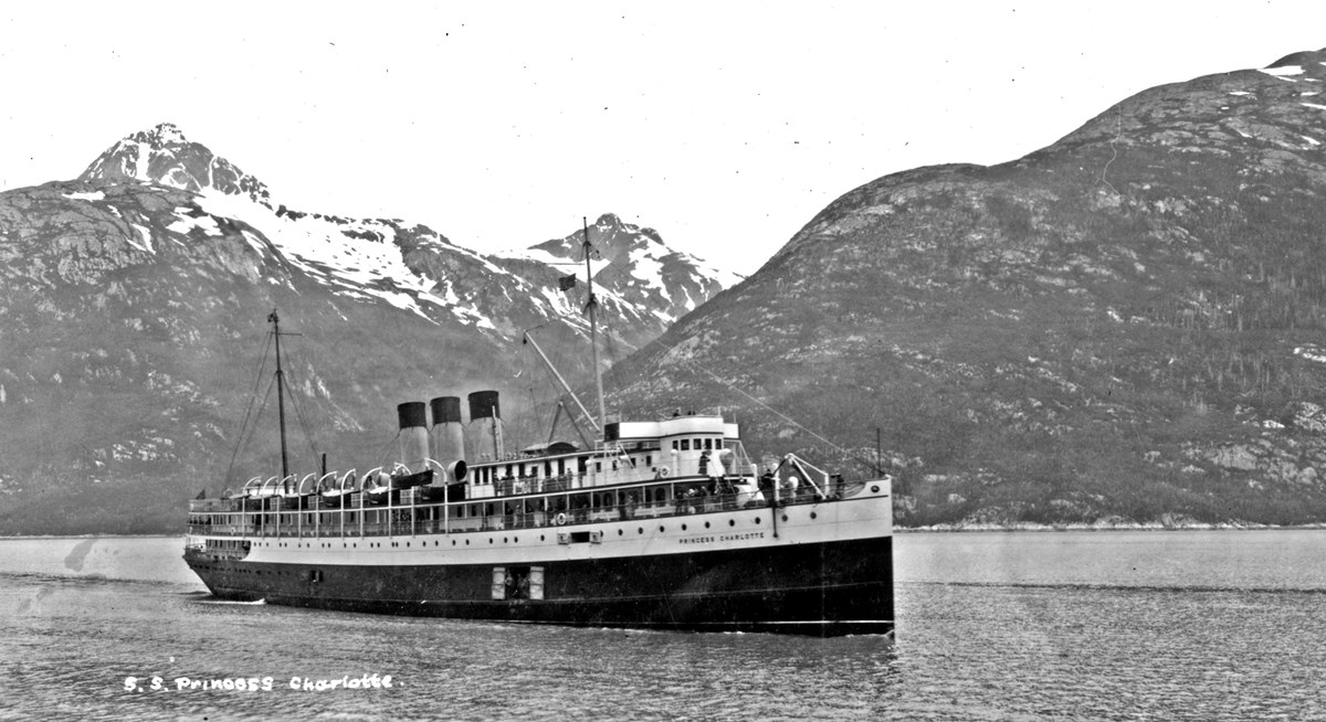 A photo of a ship with mountains in the background