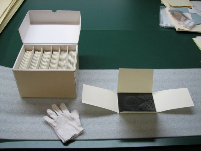 A white box and white cotton gloves on a desk.