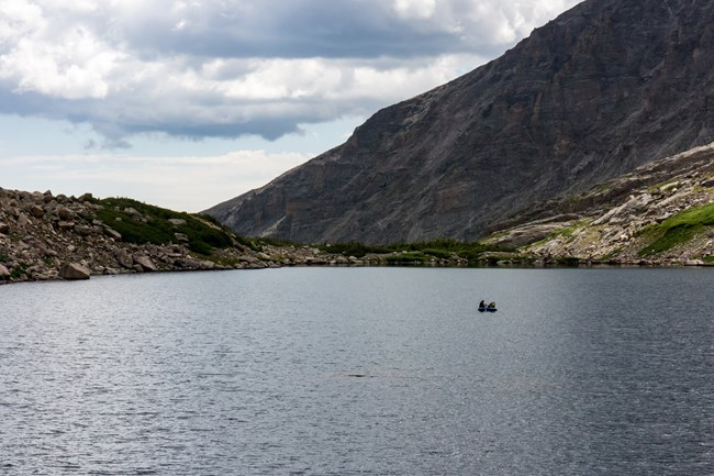 Small inflatable boat out in the middle of an alpine lake
