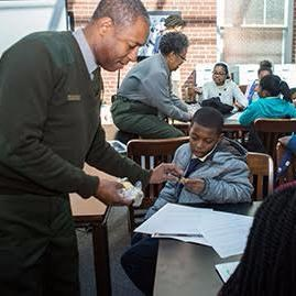 African American male ranger teaches a student at a table.