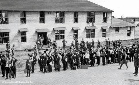 Men in uniform and civilian clothes stand outside a military buliding