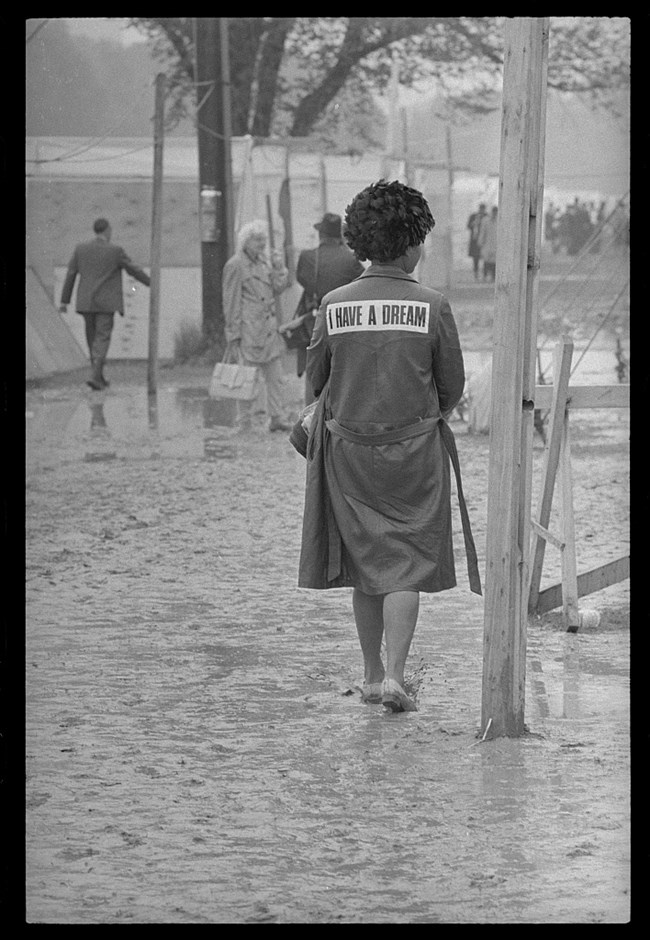 "Woman with ""I Have A Dream"" on the back of her raincoat walks through the mud of Resurrection City"