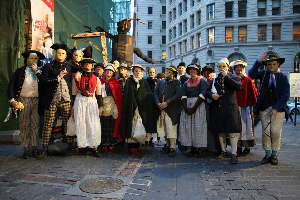 People dressed in period costumes in Boston,pose for a photograph.
