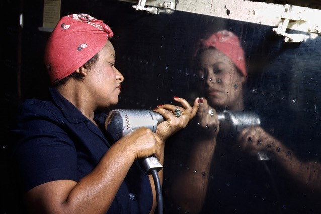 "An African American ""Rosie"" installing rivets on a war plane."