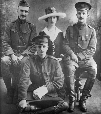 Three men in military uniforms and one woman in dress and large hat sit for a photo.